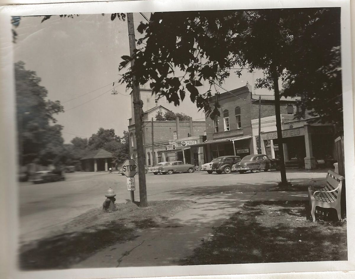 Village Square; intersection of Hamilton, Franklin, and Park Streets; circa 1955. Visible are signs for what was likely Steward's Cafe. Mr. and Mrs. Roy Steward, Sr., came to McLean in 1952 and purchased the former Lynn Cafe from Mrs. Margaret Garner.