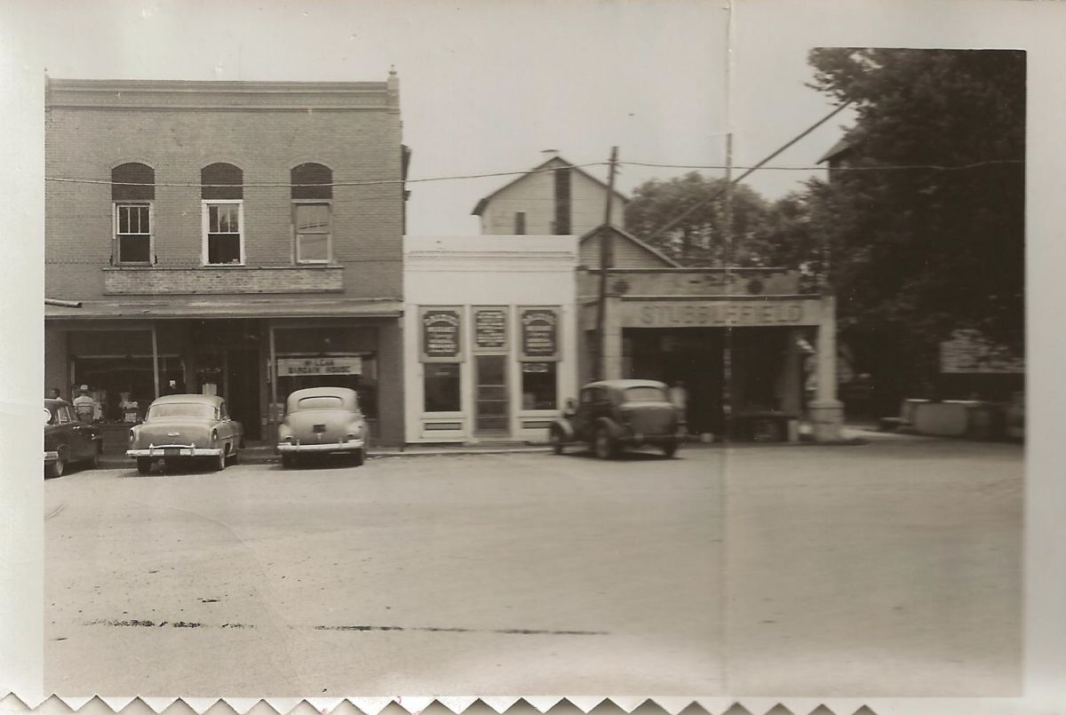 Village Square, Park St., looking south, circa 1955. The brick building with the McLean Bargain House (left) was previously C. W. Hamilton's grocery store and today houses the McLean Hardware Store. The other buildings pictured have since been torn down.