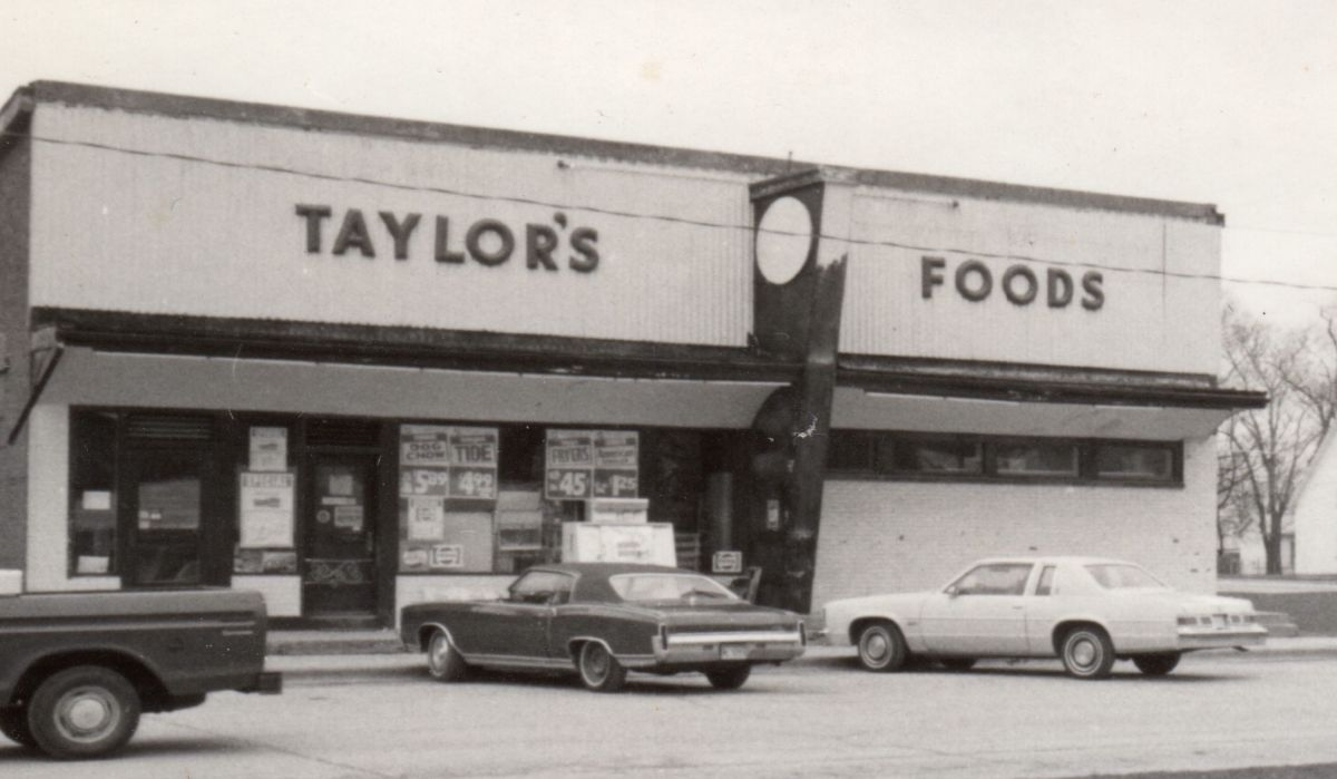 Taylor's Foods, north side of square (next to bank building), circa 1975. In 1946 W. G. Taylor opened a hardware, appliance, and dry goods store here; in 1953 he moved this to the basement and his grocery store from across the square to the first floor.