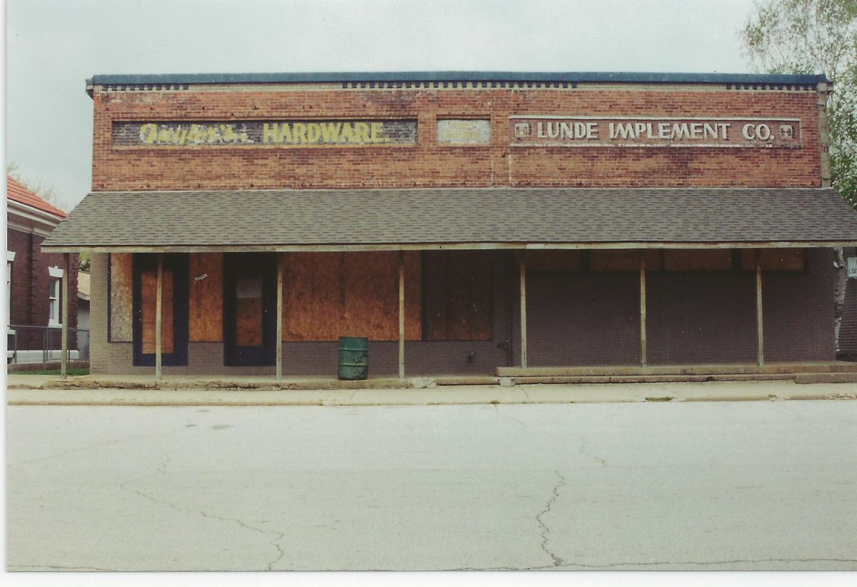 North side of Village Square, circa 2005. Signs for O. W. Earl Hardware, located here from 1941 to 1946, and Lunde Implement Co., located here from 1944 to 1964 (?), are visible. The building now serves as game storage/work space for the nearby arcades.