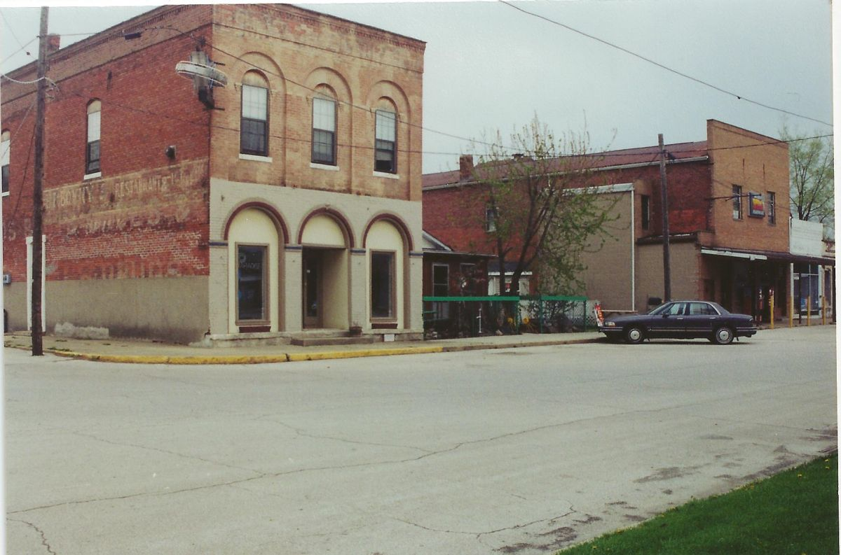 Village Square, corner of Park & Center, circa 1990s. The corner building housed E. B. Bonny Restaurant in the early 1900s, then became Sieb's Hatchery in 1929. Traces of advertisements for both businesses can still be seen on the side of the building.