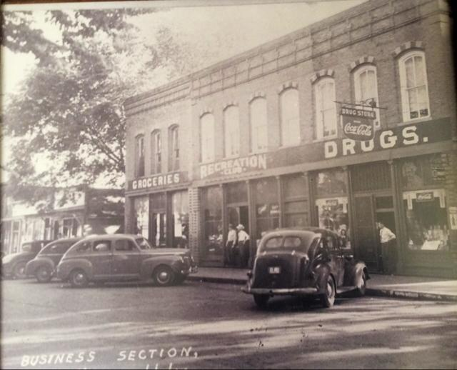 Village Square, corner of Morgan and Hamilton, late 1940s. Visible (left to right) are a grocery store (Kinsey's?), first location of the McLean Recreation Hall, and Holohan's Drug Store. This building, erected circa 1880, still stands today.